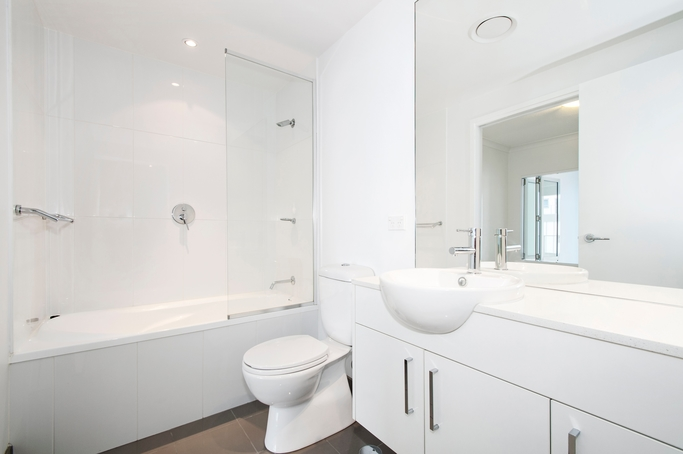 Minimalist white bathroom renovation job done with large white porcelain wall tiles