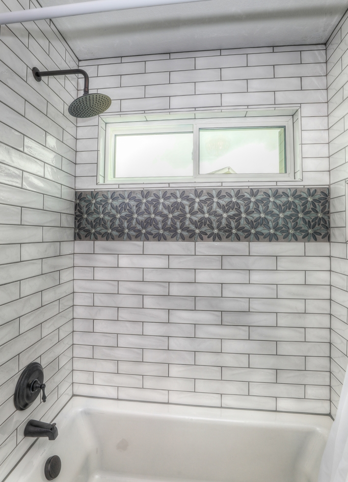 Shower repair job done on a bathroom with white porcelain tiles